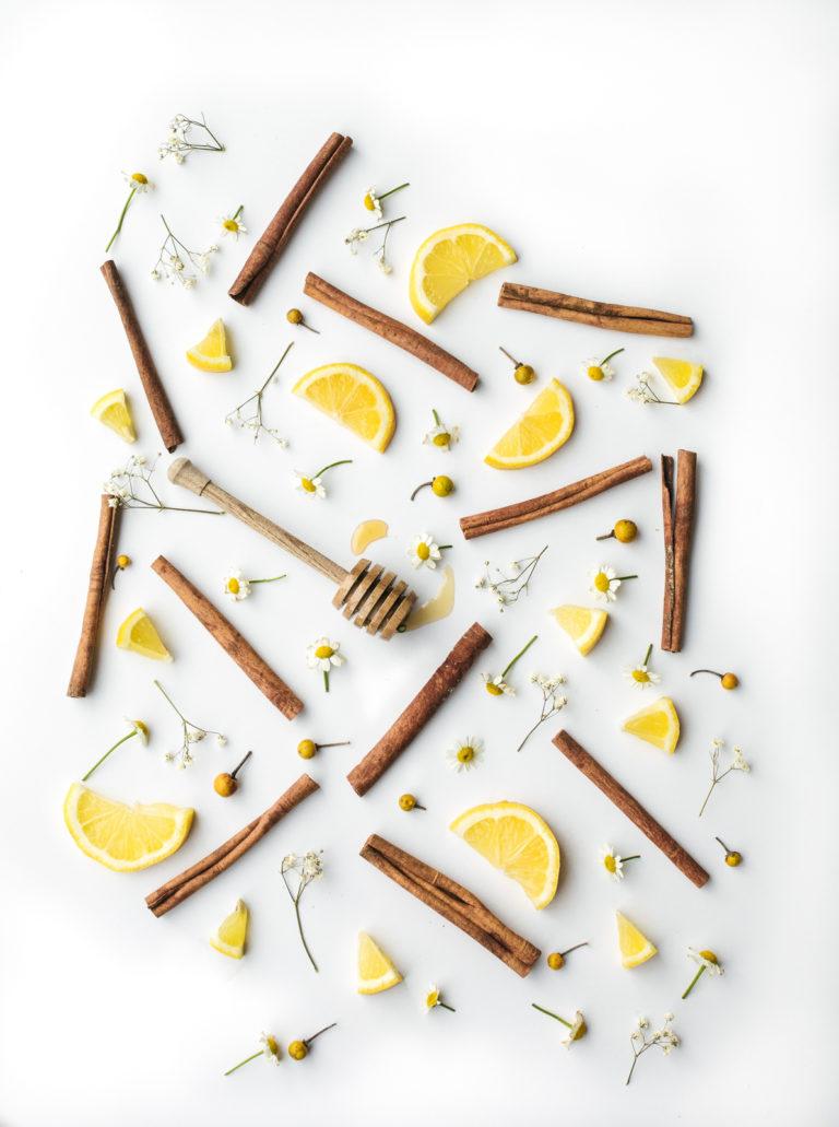 pałeczki cynamonu, drewniana łyżka oblepiona miodem orazkawałki cytryn istokrotek rozsypane nastole