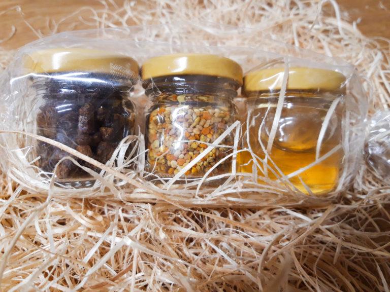 Trzy słoiczki z produktami pszczelimi owinięte w celofan