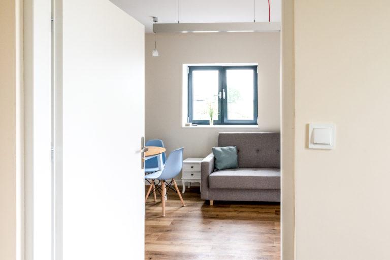 Pasieka Smakulskich - noclegi - zdjęcia wnętrz (Apartament Prowansalski - parter) - zdjęcie wejścia do apartamentu, w tle sofa, stół i krzesła