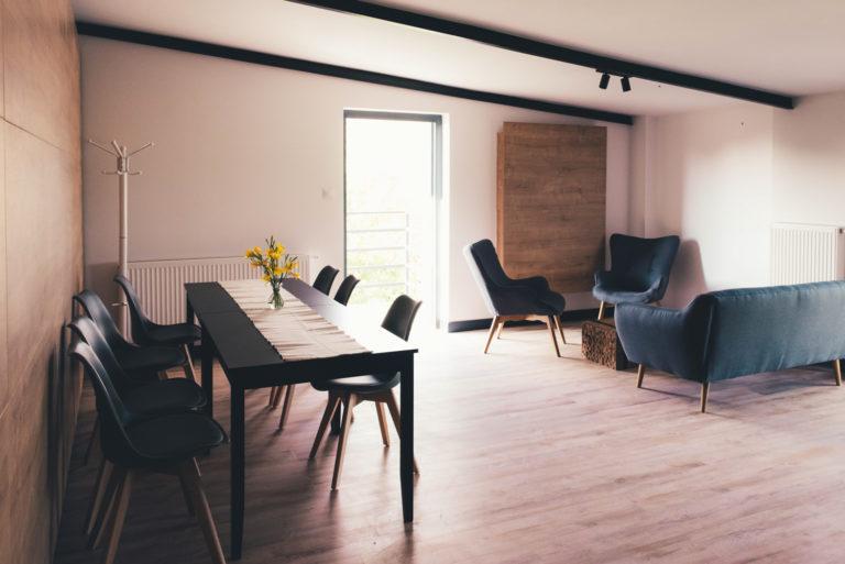 Pasieka Smakulskich - noclegi - zdjęcia wnętrz (Pokoje na 1 piętrze) - przestronny pokój ze stołem, sofą i krzesłami oraz wyjściem na taras