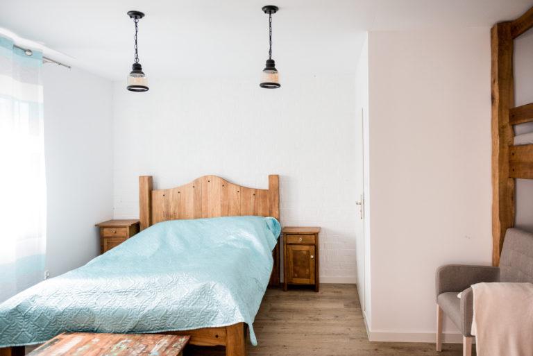 Pasieka Smakulskich - noclegi - zdjęcia wnętrz (Apartament Wiejski - parter) - duże drewniane łoże z dwoma drewnianymi stolikami nocnymi