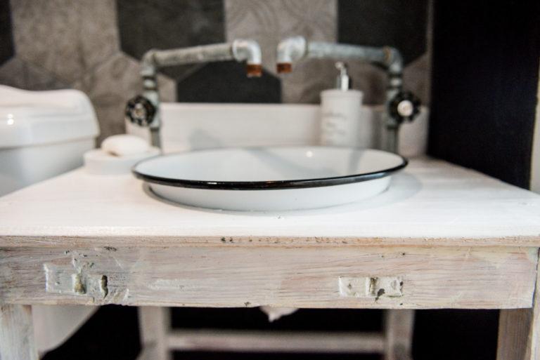 Pasieka Smakulskich - noclegi - zdjęcia wnętrz (Apartament Wiejski - parter) - umywalka (duża biała misa) oraz dwa krany na drewnianym stole łazienkowym