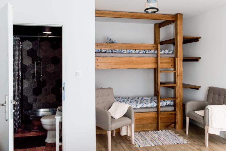 Pasieka Smakulskich - noclegi - zdjęcia wnętrz (Apartament Wiejski - parter) - piętrowe, drewniane łóżko oraz dwa przytulne fotele, wejście do łazienki