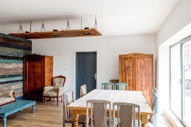 Pasieka Smakulskich - noclegi - zdjęcia wnętrz (Apartament Wiejski - parter) - widok na pokój z dużym stołem na 8 osób, dwie klasyczne szafy, kolorowa boazeria na ścianie