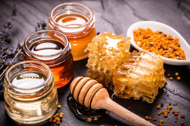 Trzy słoiczki miodów, kawałek plastra miodu, ociekający miodem nabierak i pyłek pszczeli